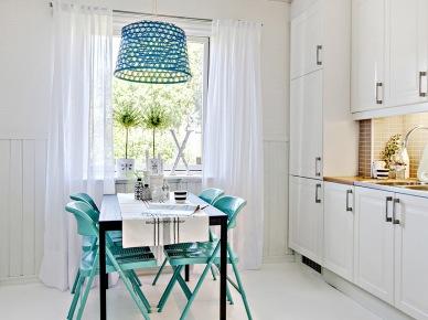 Turkusowe krzesła przy białym stole,ażurowa turkusowa lampa wisząca, i białe firanki  w aranżacji białej kuchni (24747)