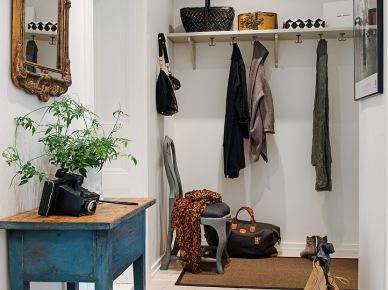 Turkusowo-niebieska konsolka vintage,stylowe rzeźbione lustro,biała półka z haczykami,francuskie krzesło turkusowe i podłoga z maturalnego drewna w przedpokoju (25936)