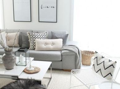 Szara sofa została udekorowana jasnymi poduszkami i pięknie prezentuje się na kremowym dywanie, który nawiązuje do ścian. Jest też i przeźroczyste krzesło, które dodaje bardziej amerykańskiego charakteru całemu...