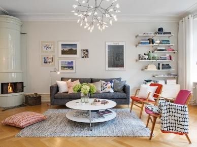 Biały ceramiczny piec skandynawski,nowoczesna lampa rozgwiazda, nowoczesne plakaty i obrazy w aranzacji salonu,wiszaca biała komoda w stylu nowoczesnym,szara sofa,okrągły stolik z półką na kółkach,drewniane miodowe fotele (25835)
