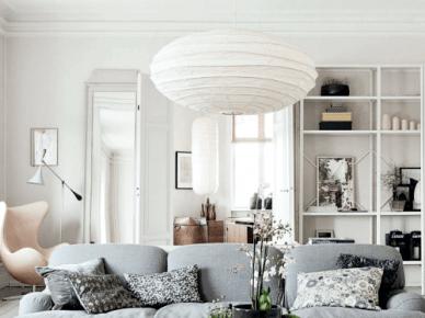 Elegancki i pastelowy salon skandynawski  z jasnoszarą kanapą,bialym stolikiem i fotelem