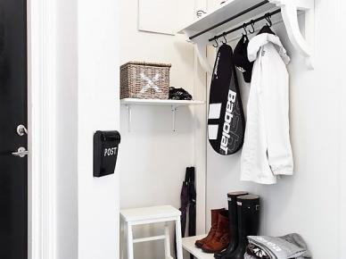Drewniane białe półki na buty i z wieszakiem,biały taboret z drewna,biało-czarna podłoga z płytek typu arlekin (25824)