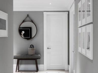 Szare ściany,biała terakota z czarną spoina i kostką ułożona w karo,okragłe lustro na rzemyku,galeria fotografii w wąskim przedpokoju (47837)