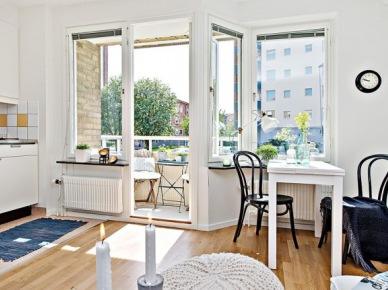 Biały wąski stół,czarne giete krzesła z drewna w otwartej jadalni z aneksem kuchennym i salonem (24699)