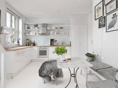 Skandynawska kuchnia z drewnianym bielonym  stołem na kutych nogach i siedziskami z szarymi poduchami (24574)