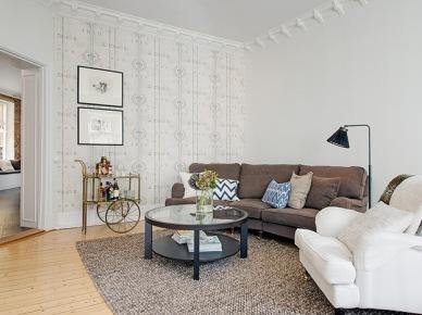 Skandynawski salon w mieszanym stylu z tapetą z ornamentem i sztukateriami na ścianach (20378)