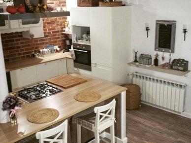 Szeroka wyspa kuchenna pełni funkcję zarówno blatu roboczego, jak i w pewnej mierze stolika śniadaniowego. Białe meble i ściany zdecydowanie wyróżniają się wśród wielu drewnianych elementów oraz na tle kontrastowej ściany z czerwonych cegieł. Pojedyncze dodatki i akcesoria w subtelny sposób dekorują...