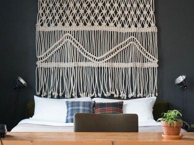 Białe makramy ze sznurka na czarnej ścianie nad łóżkiem w sypialni (20897)