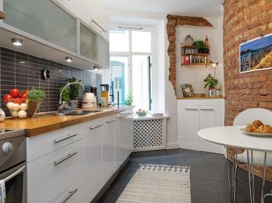 Czarne płytki cegiełki na ścianie w kuchni pomiędzy białymi szafkami,czarna posadzka i ściana z czerwonej cegły przy białym stole kuchennym (25901)