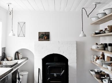 Rustykalny murowany   kominek w białej  kuchni ze ścianą z półkami na kuchenne naczynia i pojemniki (47812)