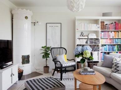 Skandynawski salon z ceramicznym piecem,regałem na książki,czarnym rattanowym fotelem i drewnianym owalnym stolikiem kawowym (24524)