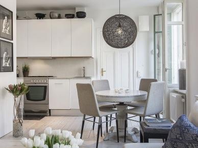 Stylowy okrągły bialy stół w aranżacji skandynawskiej jadalni z kuchnią (22450)