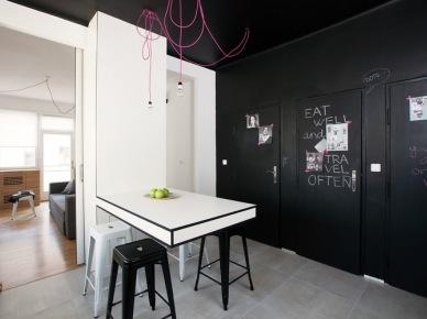 bardzo ciekawe mieszkanie do wynajęcia w Pradze - inspirujące pomysły na użycie czarnego koloru na ścianach i dekoracjach we wnętrzu. Imponująca grafika i zarazem zabawna na ścianie w salonie, gdzie tradycyjne komody tv zastąpiły skrzynie pomalowane białą farbą. Biało-czarne wnętrze wyposażone jest w dobrze zaplanowaną zabudowę z drewna orzechowego, które przykrywa niechciane grzejniki i służy za doskonałą zabudową z półkami - wykorzystano extra miejsce na kącik biurowy. Zabawnym akcentem stały się tutaj też różowe , splatane kable, na których powieszono żarówki - to kontrast rozświetlający wnętrze i przewrotnie czyniący go lekkim, zabawnym i...