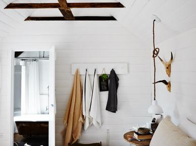 Brązowe drewniane belki w białej sypialni,okrągły stolik z drewna,lniana pościel (47813)
