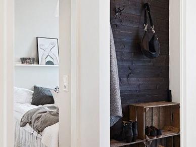 Drewniane skrzynki w roli półek na buty we wnęce zczarną boazerią z desek  małego przedpokoju (47839)