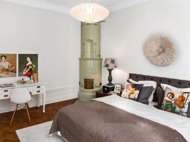 Biało-szara sypialnia z ceramicznym piecem skandynawskm i zmiksowanymi stylowo detalami (22550)