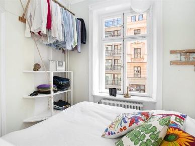 Mala biala sypialnia z otwartymi pólkami i wieszakami na ścianie (24596)