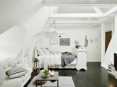 Salon razem z sypialnią w białej aranżacji małego mieszkania na poddaszu (27319)