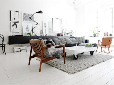 Biały stolik na kólkach,drewniane fotele z lat 60-tych,szara sofa nowoczesna i czarna komoda z lampą na przegubach w salonie z galerią skandynawskich grafik (25680)