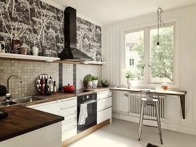 śliczna, mała kuchnia w skandynawskim stylu - wyróżnia ją biało-czarna tapeta w dmuchawce i ciekawie dobrane płytki z szarej, małej i błyszczącej...