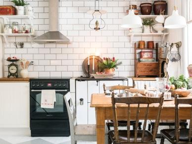 Wyraźne kafle na ścianie o prostokątnym kształcie i wzorzysta biało-szara podłoga stanowią charakterystyczną bazę dla aranżacji kuchni z jadalnią. Drewniane meble i dodatki czerpią z rustykalnym inspiracji, w które wpisuje się także skromna dekoracja...
