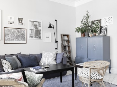 Niebieska szafa w stylu orientalnym,szara sofa nowoczesna,czarny kinkiet na ramieniu,rattanowy fotel w eklektycznym salonie (47759)