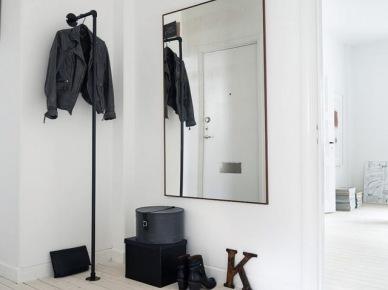 Duże prostokatne lustro na scianie,wieszak z czarnych rur,czarne pudła na białej podłodze z desek (47840)