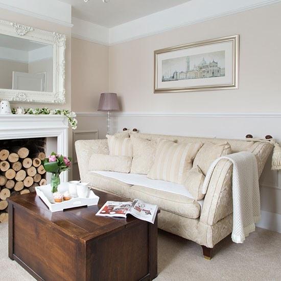 Biały stylowy kominek z klasyczną sofą i kolonialną skrzynią w roli stolikia