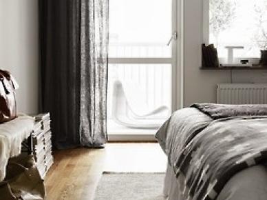 Ciemnoszare lniane zasłony,czarna narzuta z białymi szwedzkimi wzorami,biały futrzak na podłodze w dekoracji sypialni (25830)