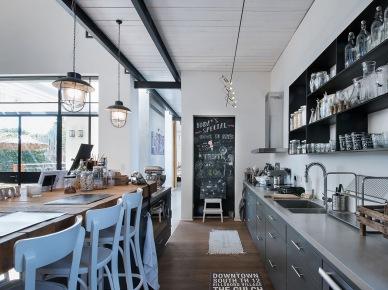 Farba tablicowa na drzwiach od spiżarki posłużyła za dodatkową przestrzeń do dekoracji. Tego typu czarne detale znacząco ożywiają przestrzeń i podkreślają industrialny charakter kuchni....