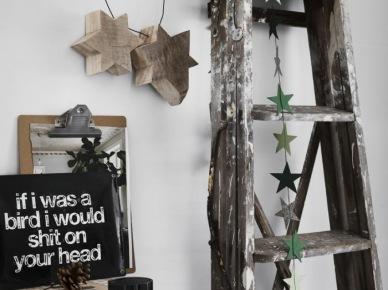Drewniana drabina ze świątecznymi gwiazdkami z kartonu,drewniane gwiazdy wiszące na metalowym drucie na ścianie ,bielony stół z drewna (47848)