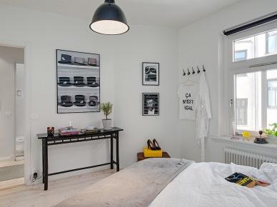 Czarna konsolka i biało-czarne grafiki w aranżacji sypialni (22981)