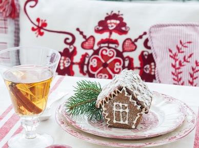 Pełna świątecznego ducha aranżacja stołu wigilijnego z niezastąpionym motywem - domkiem z piernika. Kolorystyka bieli oraz czerwieni i zieleni idealnie podkreśla aurę Świąt. Wzorzyste poduszki jako tło subtelnie wpisują się w wystrój...