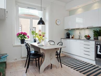 Biała minimalistyczna kuchnia skandynawska z rustykalnym stołem,czarnymi krzeslami z giętego drewna, i dywanem w biało-czarne paski (25933)