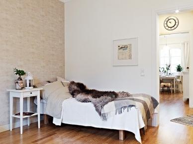 Beżowa tapeta na ścianie w sypialni z białymi stolikiem nocnym (21927)