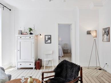 Wysoka biała komoda vintage,lampa na metalowym trójnogu i deski z naturalnego drewna na podłodze (25727)