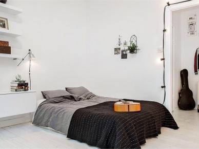 Szara pościel,czarna narzuta,żarówki na kablu wiszące wokół otworu drzwiowego w sypialni (21641)