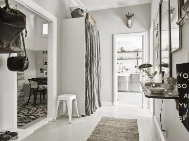 Szare ściany w przedpokoju z zabudowaną szafą z przesłoną z tkaniny,biały stołek tolix,dziergany dywanik w dekoracji przedpokoju (47760)