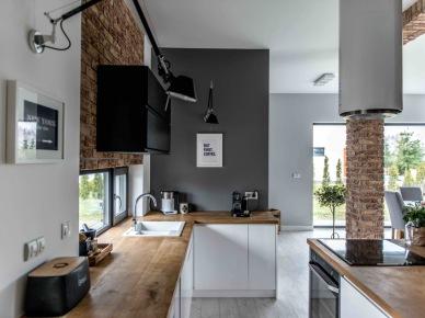 Aranżację otwartej kuchni oparto na nawiązującej do pozostałej części dziennej domu palecie barw w szarości i bieli. Sporo czarnych elementów wzbogaca wystrój i dodaje wyrazu, z kolei takie surowce, jak drewno czy cegły ocieplają...