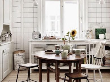 Podłoga z   desek z surowego drewna,białe płytki na ścianie,biała drewniana konsola z półkami,okragły drewniany stół rozkładany w kuchni (47894)