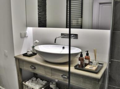 Owalna umywalka na konsolce z półką z bielonego drewna,duża tafla lustra nad umywalką,naścienna nowoczesna bateria,wiklinowe koszyki na ręczniki i akcesoria łazienkowe,szklana kabina z natryskiem (26016)