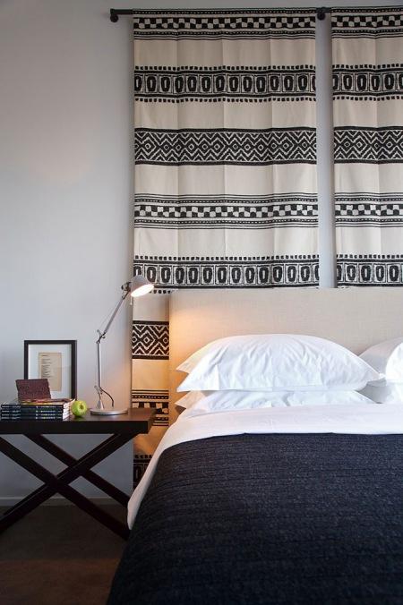 Etniczny czarno-biały kilim nad łóżkiem w biało-czarnej sypialni