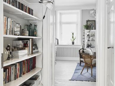Wnęka zabudowana białymi półkami na ksiązki w wąskim pokoju biurowym (47755)