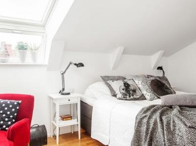 Czerwony fotel,biały stolik nocny przy łóżku w sypialni pod skośnymi ścianami (25739)