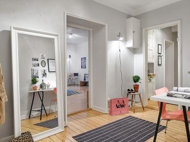 Duże białe stojace lustro w aranżacji przedpokoju z szarymi ścianami,biurkiem i różowymi detalami (25750)