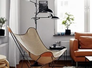 Dizajnerski brązowy fotel motyl, czarna lampa podłogowa z trzema abażurami,kwadratowy czarny stolik pomocniczy z tacą,ruda skórzana sofa w salonie (25827)