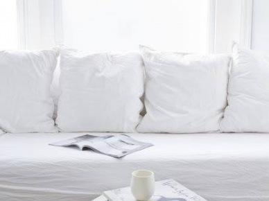 Śnieżnobiała sofa z poduszkami i białymi detalami (20574)