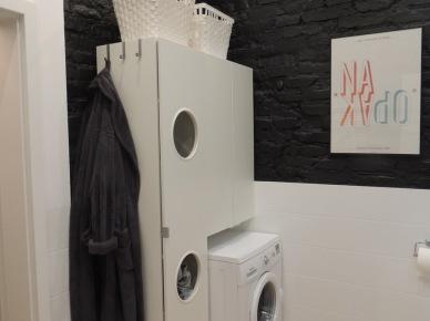 Do ustawienia pralki wykorzystano tu oryginalną szafkę, nawiązującą kształtem do pralki. Z boku zawieszono praktyczne wieszaki, a na górze ustawiono białe kosze ładnie kontrastujące z czarną ceglaną...