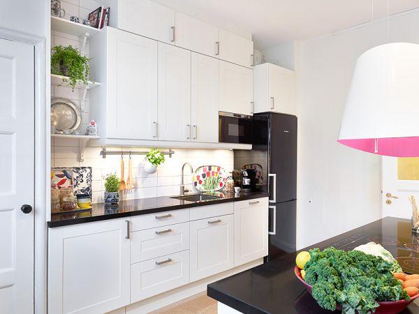 Czarna lodówka i blaty w białej kuchni  zdjęcie w