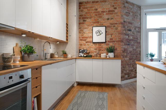 Biała kuchnia ze ścianą z czerwonej cegły  zdjęcie w